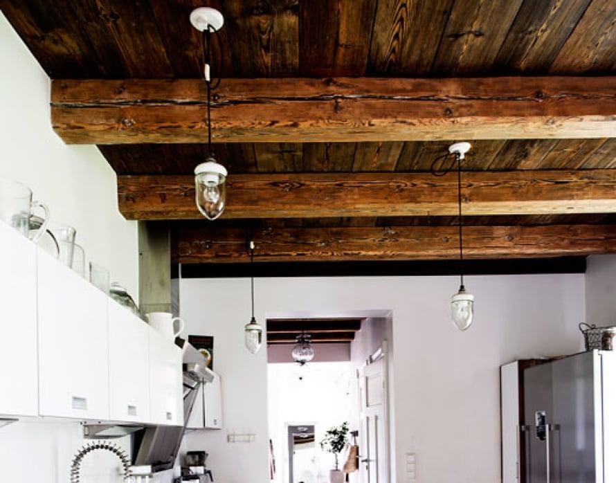 <p><p>Nina ja perheen kodin keittiölle antaa ilmettä tummaksi sävytetty katto paksuine parruineen. Ninan maalaisindustrialismiksi kutsumaan sisustustyyliin kuuluu puun ja teräspintojen yhdistely ja mielenkiintoiset yksityiskohdat kuten navettavalaisimet.</p></p>