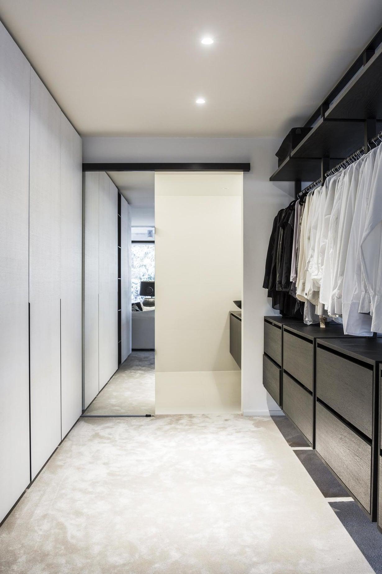 Alakerran pääkylpyhuoneeseen kuljetaan vaatehuoneen kautta. Tiloja erottaa peilistä tehty liukuovi. Säilytysjärjestelmä on koottu Heinin suunnitteleman valmiskalustejärjestelmän osista ja se on tulossa tuotantoon lähiaikoina.