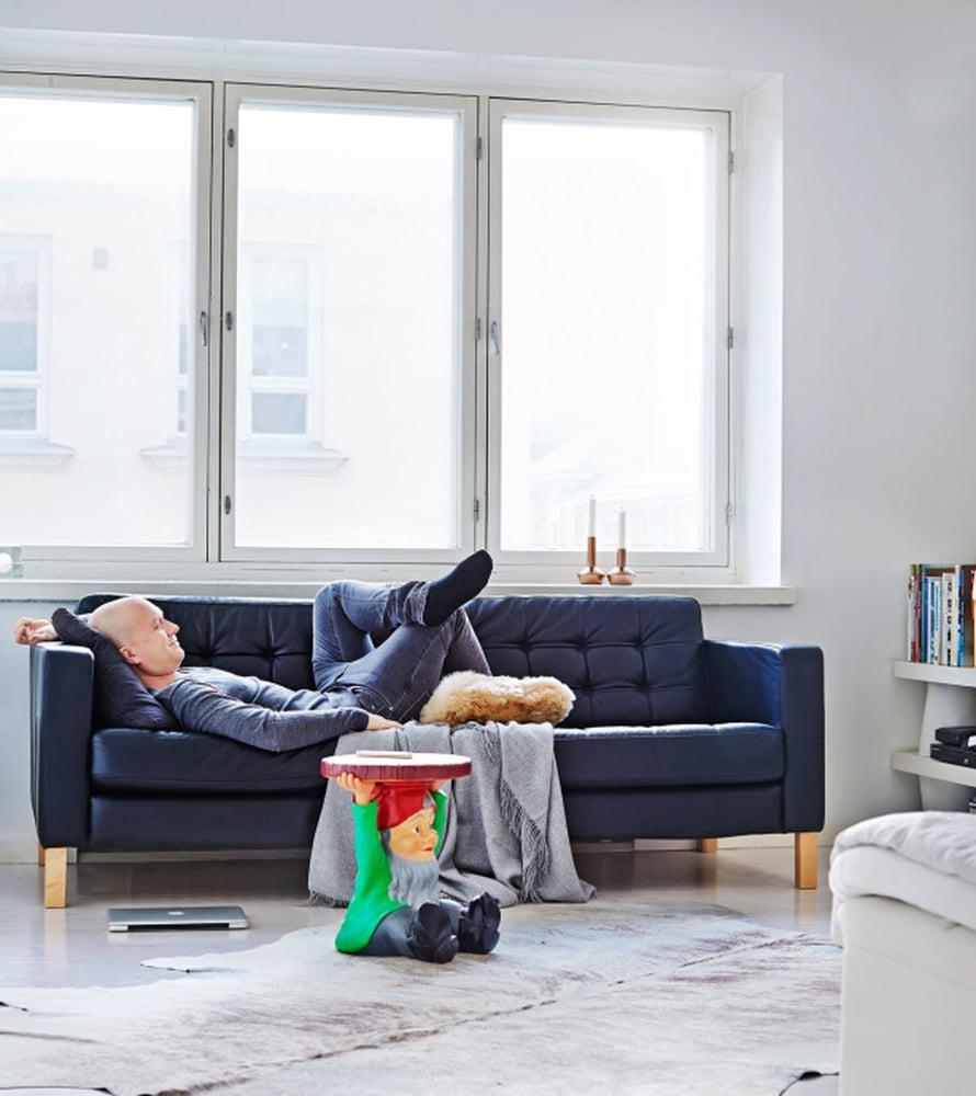 """Mikko Vesanen pohtii usein työhommia sohvallaan, josta avautuvat kattonäkymät Punavuoreen. """"Oudoin esineeni on Philippe Starckin Kartellille suunnittelema Attila-tonttupöytä. Se on jotenkin perverssi esine ja ristiriidassa pelkistetyn tyylini kanssa. Kodissa pitää ehdottomasti olla jokin ristiriitaisia tunteita herättävä esine"""", Mikko sanoo."""