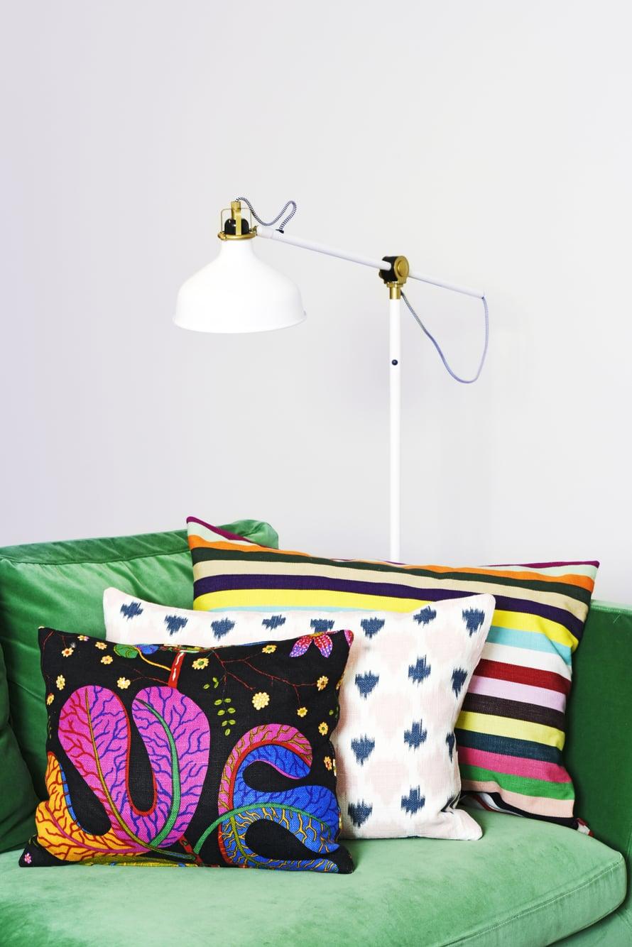 Ikean vihreä samettisohva sai kaverikseen Svenskt Tennin mustapohjaisen tyynyn, hempeän vaaleanpunaisen pellavatyynyn Moko Marketista ja reipasta raitaa Ikeasta.