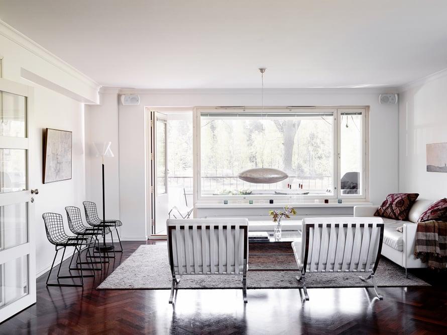 Olohuoneen päädyssä on parveke, jolta voi ihailla vihreyttä ja merenpoukamaa. Käsintehty messinkivalaisin on espoolaisesta Home Bazaar -sisustusliikkeestä. Mies van der Rohen Barcelona-tuolit olivat pitkäaikainen haave, joihin säästettiin.