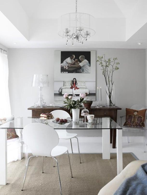 Valkoinen sisustus ja lasipöytä ovat raikas valinta pieneen ruokailutilaan. Liukuovet aukeavat terassille. Seitinohuet verhot suojaavat liialta auringolta. Sivupöydän päällä on Ferruccio Lavianin Kartellille suunnittelema Bourgie-valaisin. Läpinäkyvät tuolit ovat Kartellin Louis Ghostit.