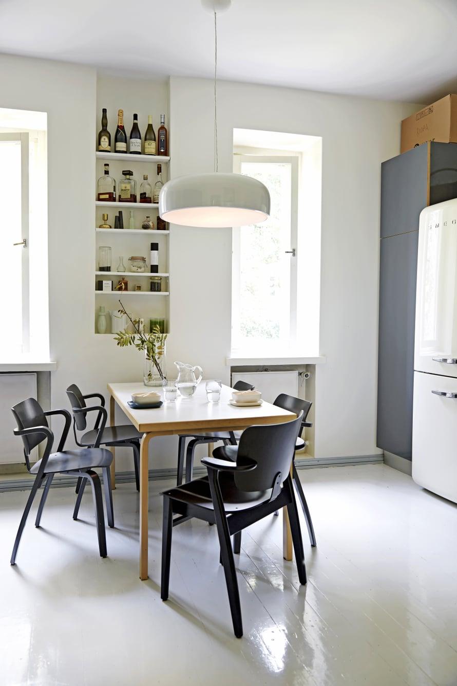 Asunnossa on iso, valkoharmaa keittiö, jossa on paljon säilytystilaa. Flosin Smithfield-valaisin on hankittu Vepsäläiseltä. Suurikokoinen valaisin sopii yhteen Alvar Aallon klassikkopöydän kanssa. Ilmari Tapiovaaran musta Domus-tuoli hankittiin Aerosta ja neljä Aslak-tuolia Aarnes Designista Töölöstä.
