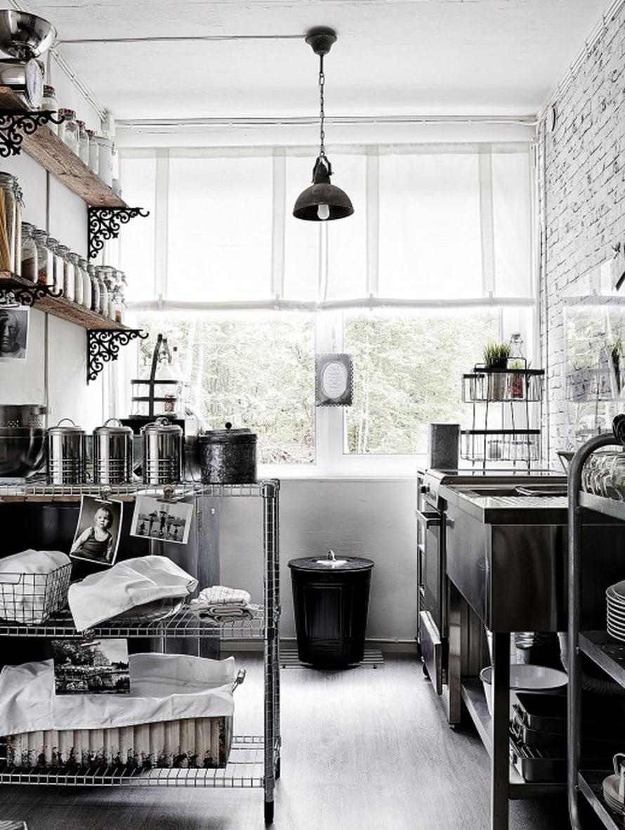 Keittiössä on paljon keveitä kärryjä ja hyllyjä, joihin mahtuvat pikkutavarat ja astiat. Seinähyllyillä on pitkät rivit kuivaruokia kauniisti lasipurkeissa.