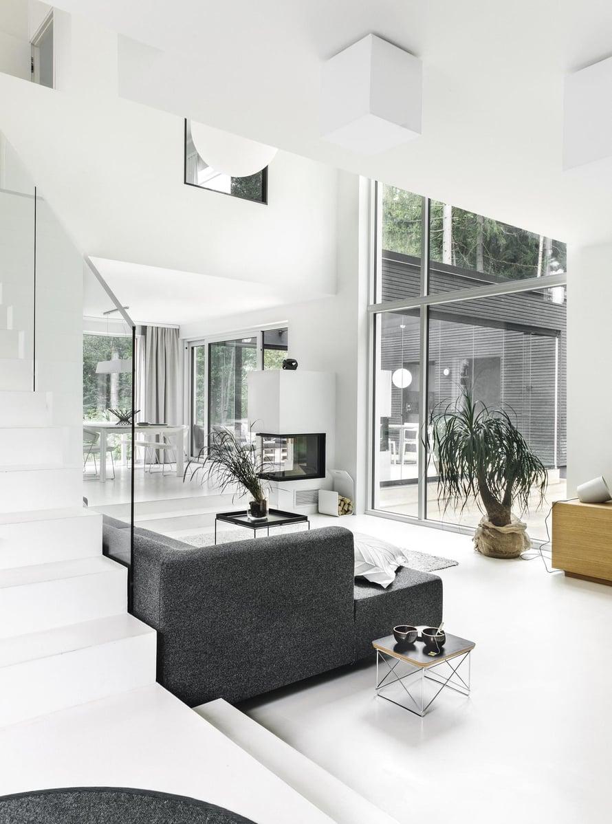 Takkatulesta  voi nauttia  monesta eri suunnasta. Schmidin Ekko U55 -kiertoilmatakka maalattiin seinien väriseksi. Alakerran mikrosementtilattia Pandomo floor on luonnonvalkoinen. Isot ikkunapinnat aurinkosuojakäsiteltiin, jolloin auringonvalo ei paista sisään liian kuumasti. Portaiden  lasikaiteet ovat Zeta Designista.