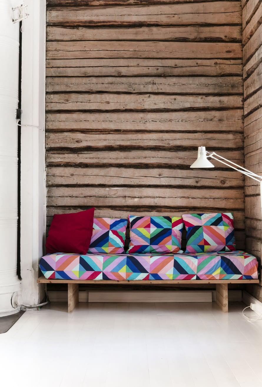 Olohuoneen sohva on verhoiltu Maija Louekarin Marimekolle suunnittelemalla Tilkkutäkki-kankaalla.