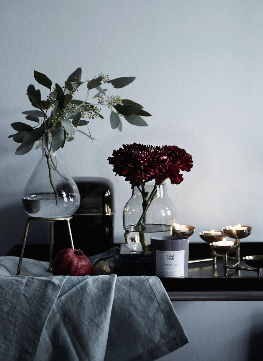 Ihastele tänä jouluna perinteisen joulutähden sijaan tummia, viininpunaisia neilikoita ja krysanteemeja. Kaunis asetelma syntyy, kun lisäät  mukaan samasta sävymaailmasta granaattiomenan ja viikunan.  Julia-maljakolla  on pyöreä pohja ja metallinen jalusta, 29,90 e, Indiska.  Oyster-tuoksukynttilä  on tyylikkäässä 1970-lukua henkivässä, tummassa purkissa, 197 e, Kartell. Muuton  Silent-maljakko  35 e ja Gauharin  Tranquility-tuoksukynttilä  38 e, Formverk.  Asala-tuikkuteline  44,90 e, Indiska, ja  tarjoiluvaunu  290 e, Moko. Pellavaliina kuvausrekvisiittaa.