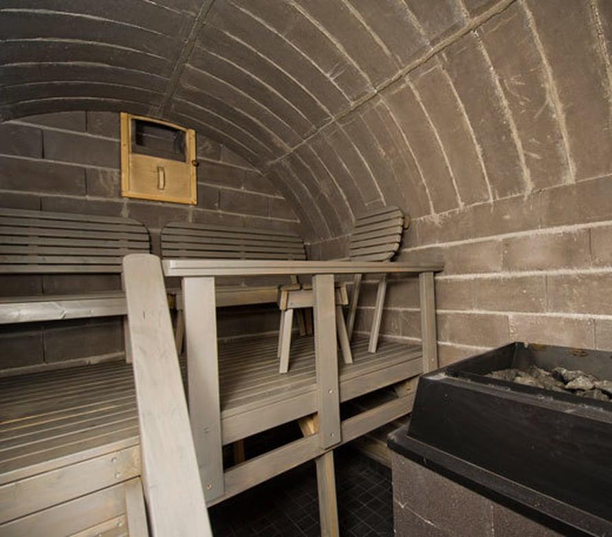 <p><p>Holvimainen savusauna voidaan rakentaa niin, että sauna sulautuu maastoon kuin vanhan ajan maasauna. Huomaa puutarhapenkkejä muistuttavat lauteet! Kuva: Holvisaunat</p></p>