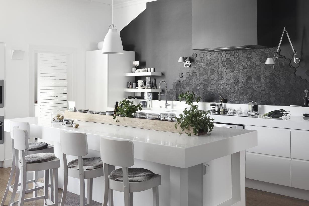 Keittiön seinä laatoitettiin epäsymmetrisesti Patricia Urquiolan laatoilla, jotka jäljittelevät keittiön ikkunasta avautuvaa mustien kattojen rytmittämää näkymää. Saarekkeen tuolit on suunniteltu ravintoloihin, ja ne lyhennettiin asukkaille sopiviksi. Keittiökalusteet ovat suomalaisen Zacuksen, Tolomeo-seinävalaisimet Artemiden ja kattolamppu Lightyearsin Caravaggio.
