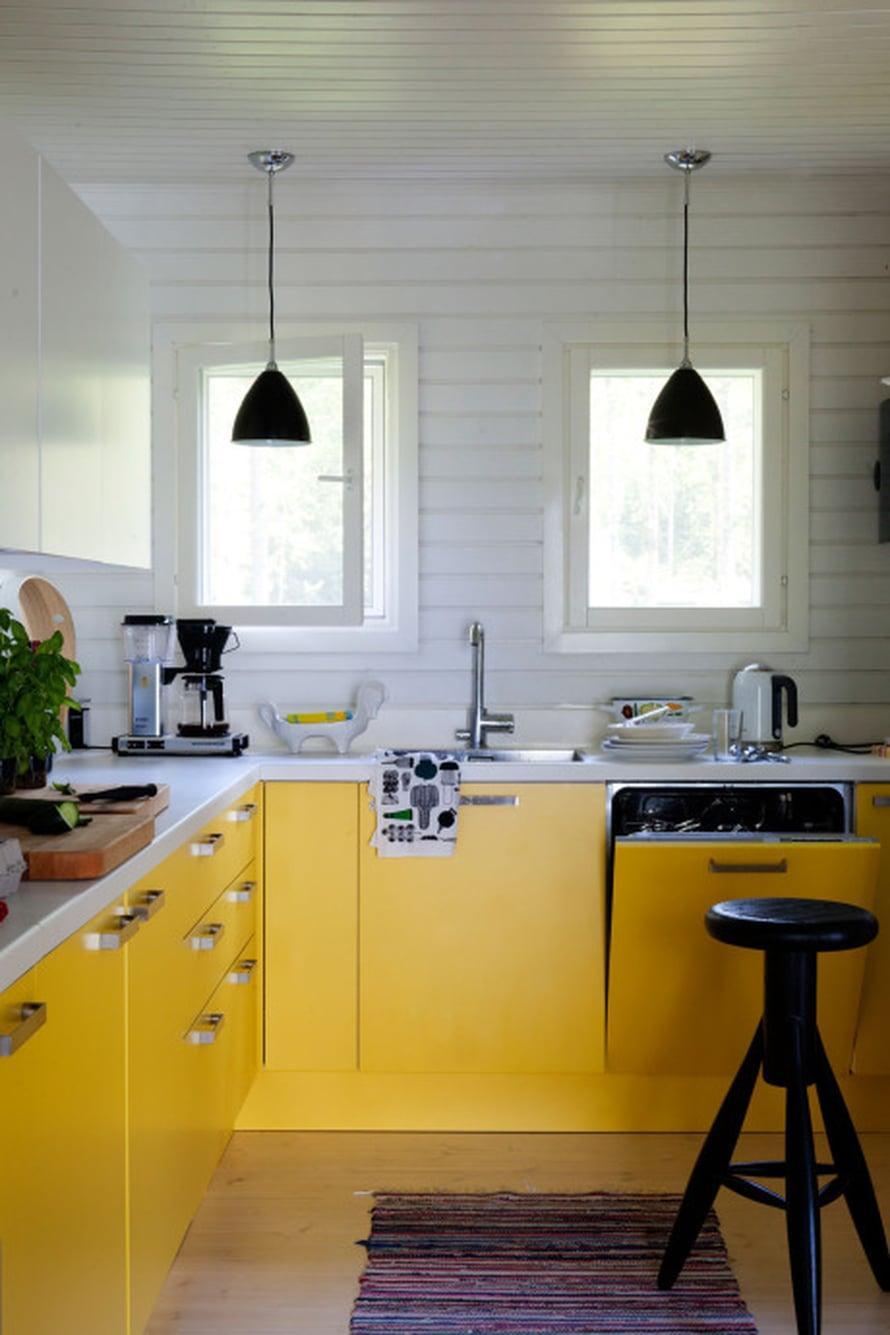 Valkoinen ja keltainen ovat raikas väripari, jota on terästetty mustilla valaisimilla ja jakkaralla. Peruisväriyhdistelmät toimivat aina. Kaapistot ovat Nixi-keittiöiden Valanti-mallistosta, maalisävy L301. Valaisimet ovat Bestliten, Rocket-jakkara Eero Aarnion. Kuva Tuomas Kolehmainen.