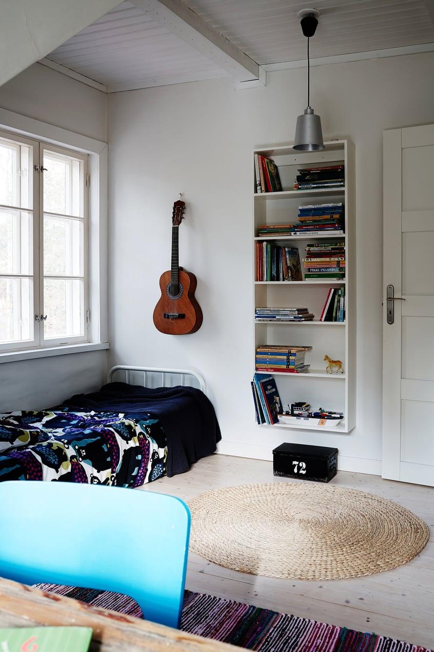 Kun kiinnittää kirjahyllyn leijumaan seinälle, lattiatilaa jää vielä hieman enemmän. Pojan huoneessa harrastukset saavat näkyä.  Kuva: Krista Keltanen