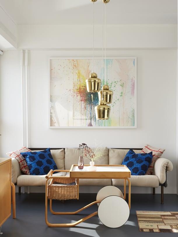 Aallon tarjoiluvaunu ja Kukkapuron Ateljee-sohva ovat molemmat vintagea. Marimekon tyynyjen värit sointuvat yhteen Jaakko Mattilan Pyttipannu-maalauksen kanssa. Minikelim ei peitä hienoa lattiaa liiaksi.