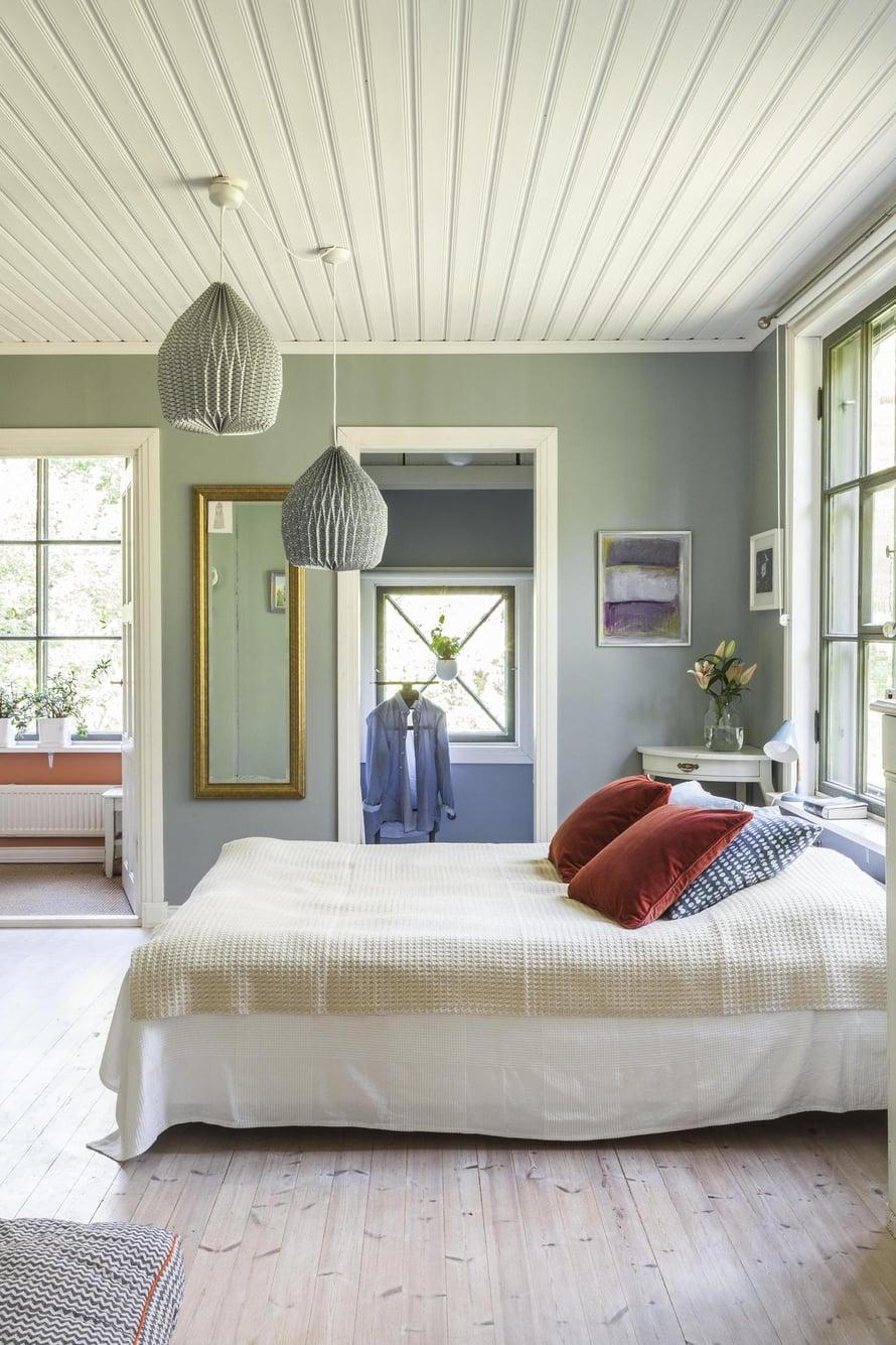 Makuuhuoneen seinien värisävy on rauhoittava salvianvihreä. Sängyn päällä on Tipukonvehtin villapeite. Tyynyt ovat Mokosta ja valaisimet Habitatin. Kulmapöytä on löytö kirpputorilta. Koska talossa ei ollut vaatekaappeja, makuuhuoneen perälle päätettiin rakentaa vaatehuone.