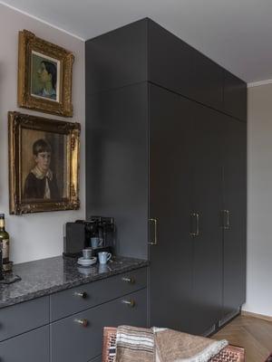 Kultakehyksiset muotokuvat ja perintömaalaukset tuntuivat muualla asunnossa liian raskailta, mutta ne löysivät paikkansa keittiön työtason päältä. Integroidut täyskorkeat kylmälaitteet ovat Electroluxin mallistosta