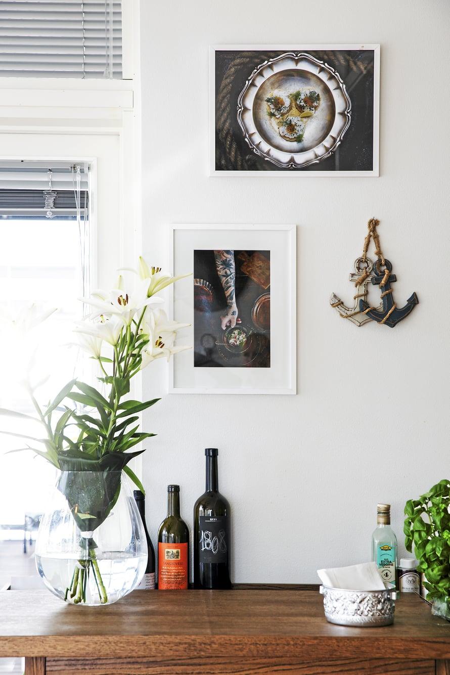 SAAREKKEEN ON NIKKAROINUT Tebian-merkin isä Teppo Lakaniemi. Miehen käsialaa on myös Björckien keittiön suurikokoinen ruokapöytä ja kirjahyllyt.Seinällä roikkuvat ankkurit Tomi osti Australiasta,ja valokuvataulut ovat lahjoja Huippukokin kotiruokaa -kirjojen kustantajalta.