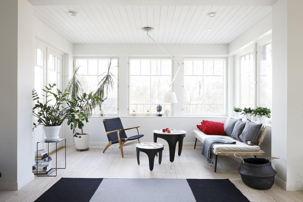 Olohuoneen lasiverantamaisessa syvennyksessä istutaan kahvilla. Viherkasvien välistä aukeaa ovet terassille. Svenskt Tennin tarjotinpöydät ovat Tukholmasta. Sohvana toimii vielä toistaiseksi Ikean daybed, kunnes se muuttaa alakertaan valmistuvaan oleskelutilaan. Kevyt nojatuoli on Hans J. Wegnerin, matto Valannin.