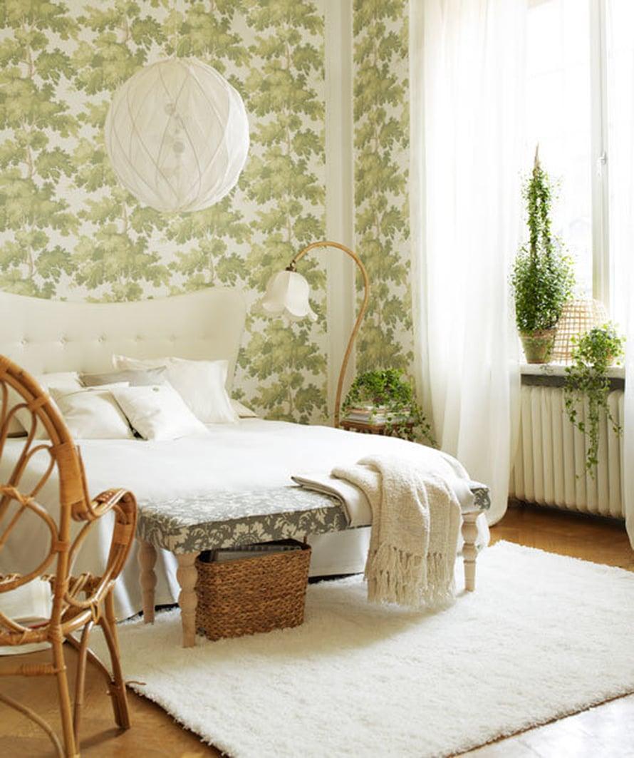 """Rohkenisitko tapetoida koko sein&auml;n kasvitapetilla? Ihanan levollinen tunnelma makuuhuoneeseen syntyy raikkaasta vihre&auml;st&auml; ja valkoisesta, kun mukaan yhdist&auml;&auml; trendik&auml;st&auml; rottinkia. Kuva: <a href=""""http://www.sandbergab.se/sv"""">Sandberg</a>."""