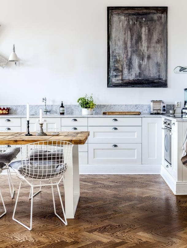 Keittiön yläkaapittomuus sopii avoimeen oleskelu-ruokatilaan ja tekee keittiöstä huonemaisemman. Työtasojen marmori nousee seinälle, mikä antaa huolitellun ilmeen. Työvalot ovat Bestliten seinävalaisimet. Seinällä on Michael Westonin maalaus.