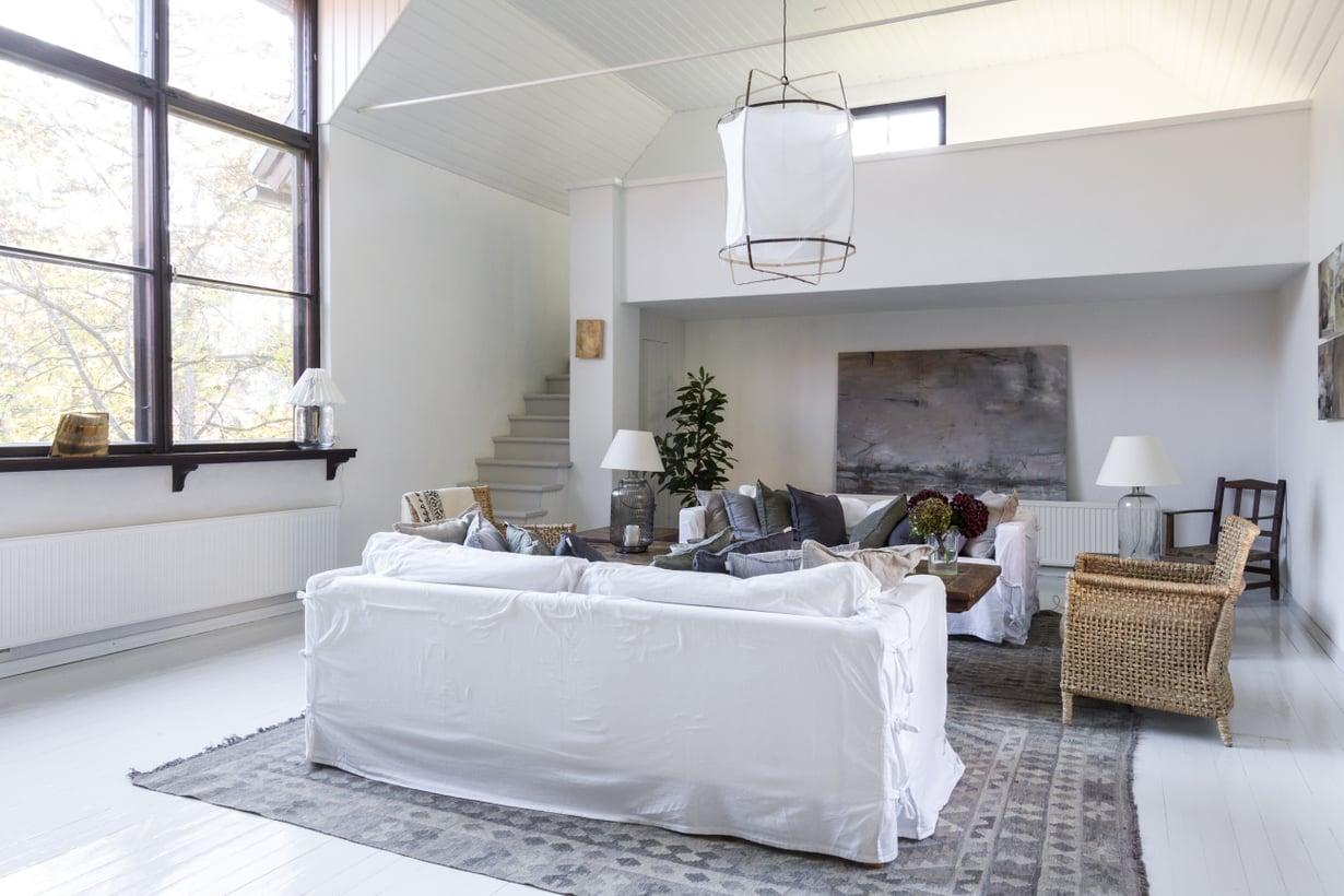 Entinen ateljee on nyt olohuone. Valkoiseksi maalattu tila sisustettiin kahdella Ikean sohvalla, joihin löytyi irtohuput Ellokselta. Casuarinasta hankittu vanha puupöytä ja rottinkikalusteet tuovat lämpöä huoneeseen. Takaseinän suuri maalaus on Aila Leppikankaan. Parven työhuoneesta on näkymä merelle asti.