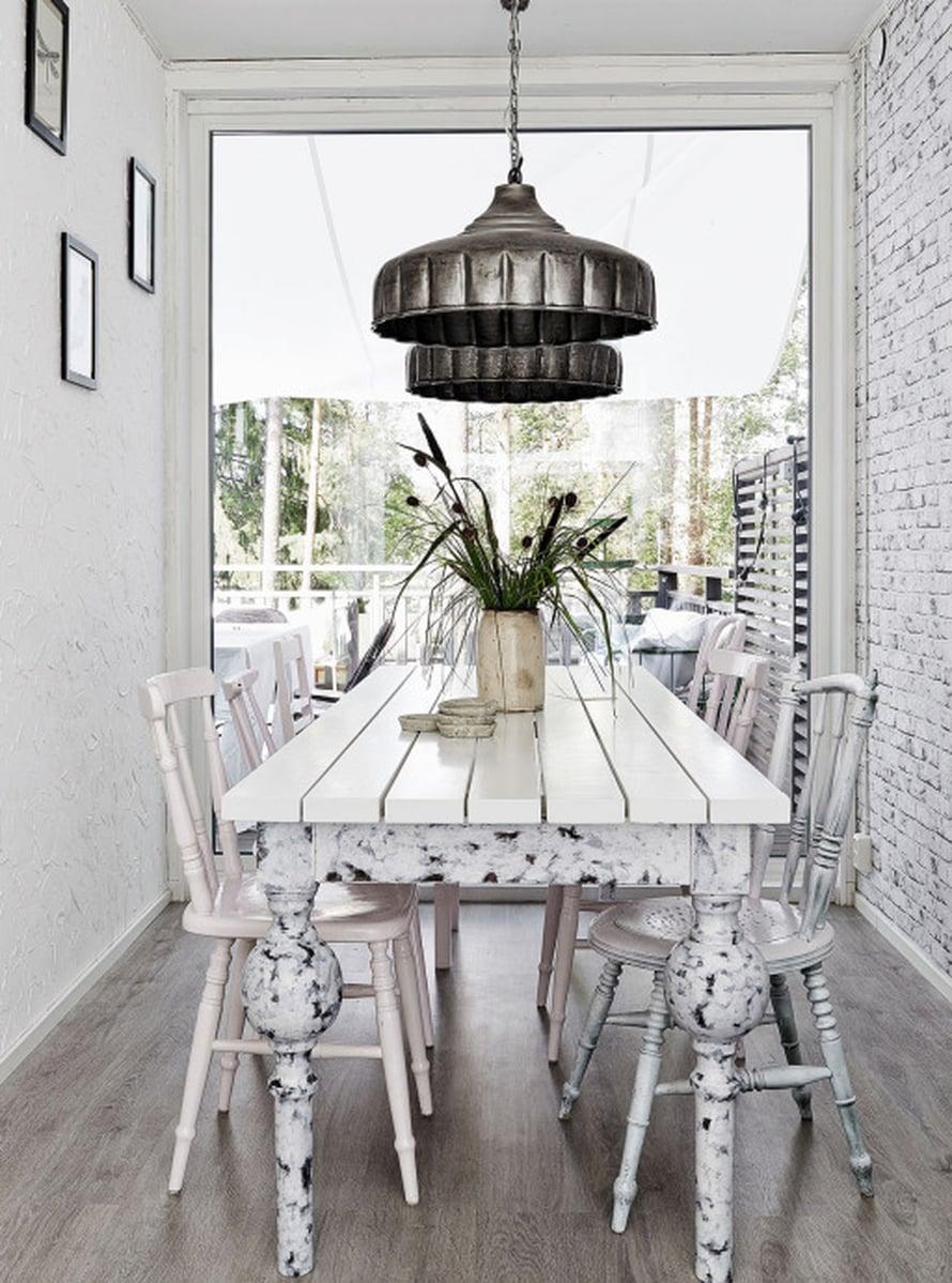 Ruokahuone sijoittuu alakerran konttiin, jonka päätyseinä korvattiin ikkunalla. Pitkä ja kapea pöytä teetettiin puusepällä. Valaisimet on hankittu Wanilla Rosesta.