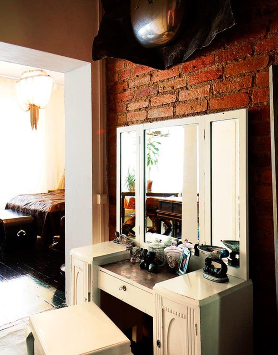 <p><p>Peilipöytä sijaitsee hämyisessä käytävässä, joka johtaa valoisaan makuuhuoneeseen. Pöydän yläpuolella on Juha Ojansivun Salaisuuksia-veistos.</p></p>
