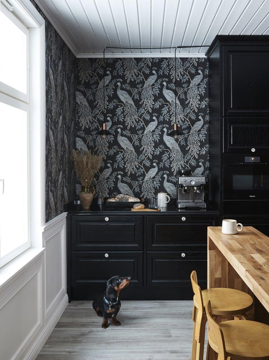 Keittiössä on Nixin tammiset, tummaksi petsatut kehäovet. Mielen höyryuuni on sijoitettu katselukorkeudelle kaapistoon. Näyttävä riikinkukkoaiheinen Arthousen Lazzaro-tapetti tilattiin Wallpaperdirect-nettikaupasta.