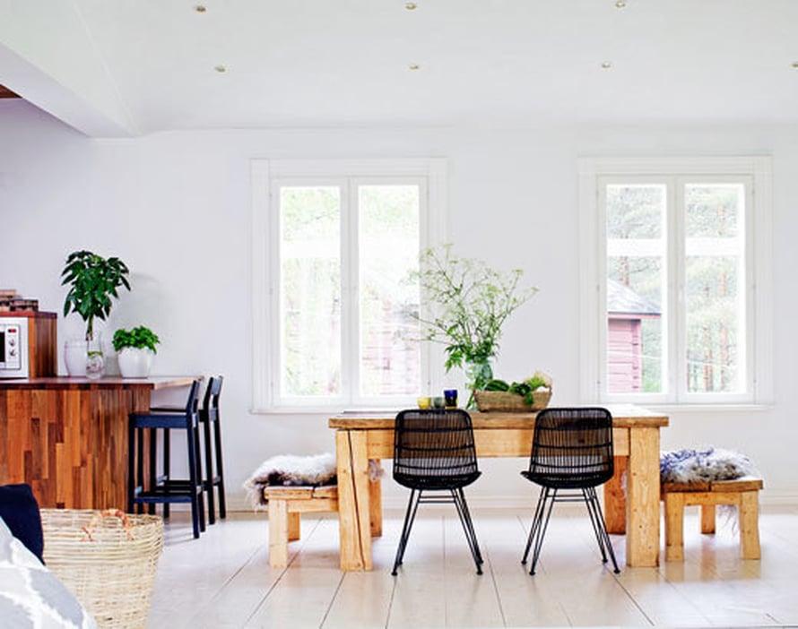 <p><p>Ruokailutilassa on konstailematon tunnelma. Pöytä ja penkit ovat isännän nikkaroimat. Tukevat kalusteet saivat keventäjiksi Bloomingvillen sirot pikkutuolit. Leveät lattialankut sopivat isoon tilaan paremmin kuin kapeat.</p></p>