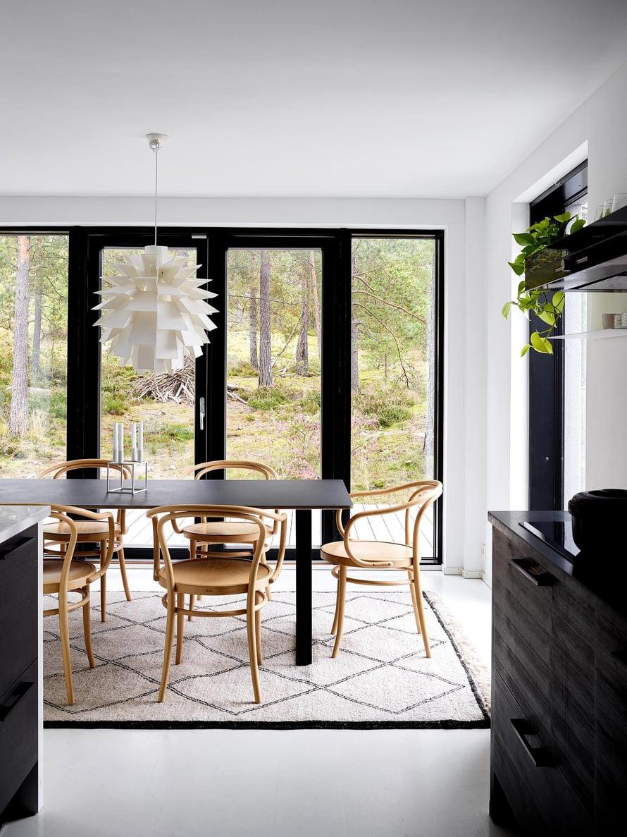 Hanna valitsi ruokatilaan suuren, mustan Muuton ruokapöydän. Tuolit ovat Tonin, ja niiden mallinumero on 30. Luonto tulee osaksi sisustusta suurien ikkunoiden kautta myös ruokatilassa. Norm 69 -valaisin on Normann Copenhagenin.