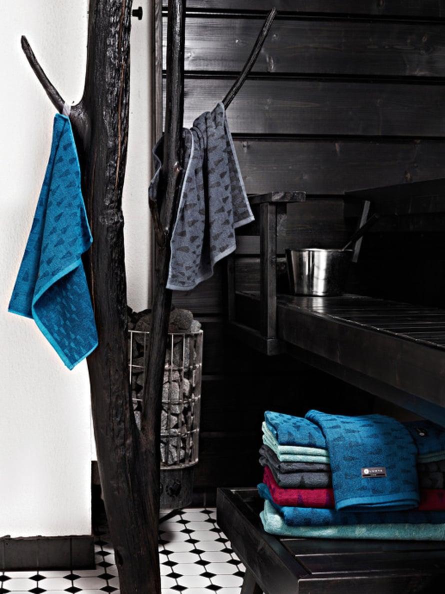 """Huippusuosittu musta sauna kruunataan yll&auml;tt&auml;v&auml;sti mustin salmiakkiruuduin viimeistelyll&auml; valkoisella 8-kulmaisella kaakelilla. Mielet&ouml;n yhdistelm&auml;! Huomaa my&ouml;s kiva idea: vanhasta puusta on tehty maalaamalla tyylik&auml;s pyyheteline. Kuva: <a href=""""http://www.luhta.fi/"""" target=""""_blank"""">Luhta</a>"""