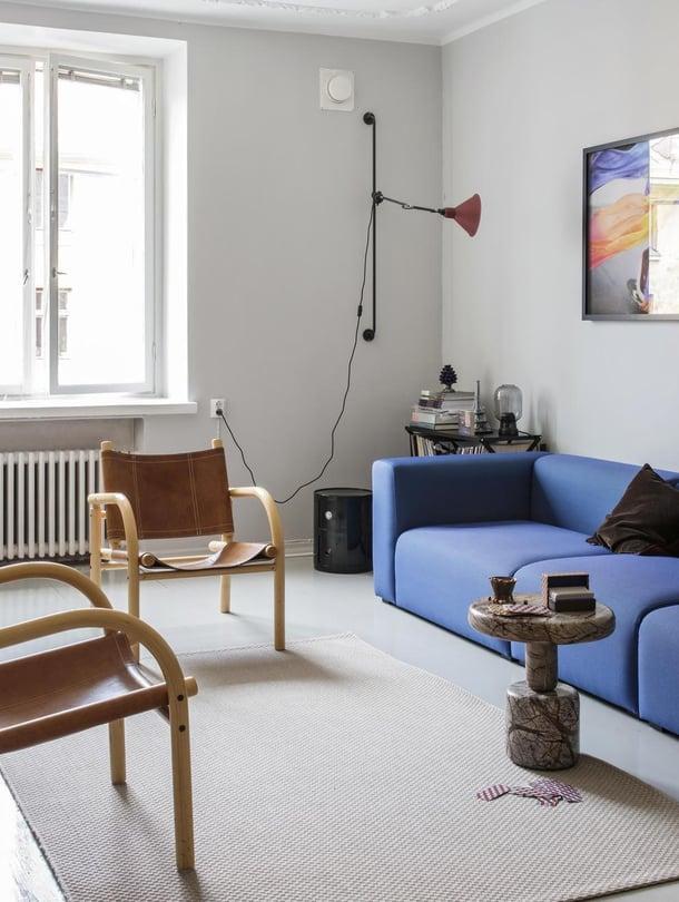 Ben af Shulténin  safarituolit pehmentävät modernin olohuoneen väritystä. Muuton sininen Connect-sohva koostuu moduuleista. Juliste on tilattu Fotografiskan museokaupasta. Rock table -marmoripöytä on Tom Dixonin suunnittelema.