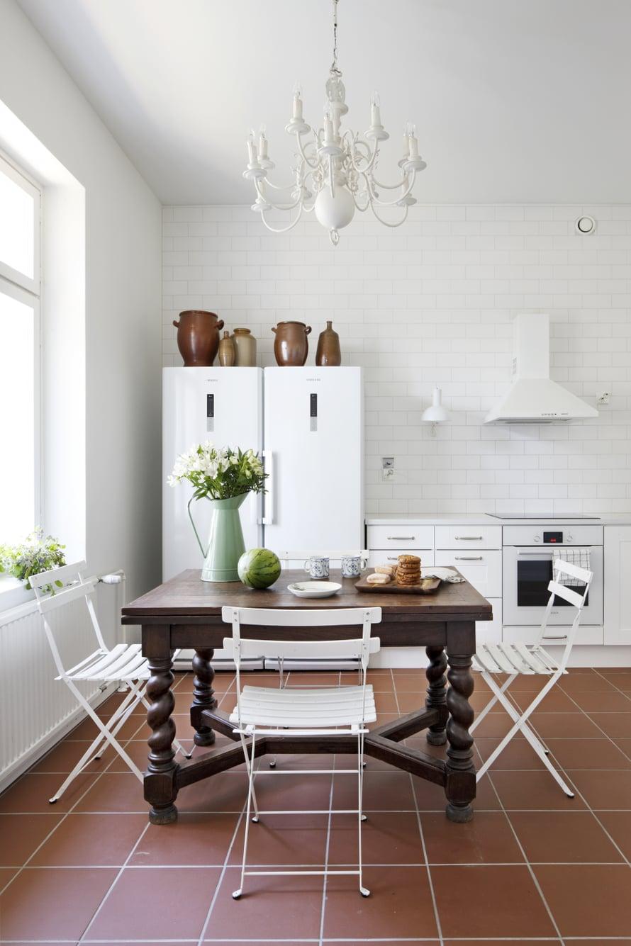 Keittiön barokkipöytä on tuotu Belgiasta, kuten kattokruunukin. Bistrotuolit palvelivat vuosia mökillä ja siirtyivät kotiin, kun mökki myytiin. Lattialla on Pukkilan Litocer-laattaa.