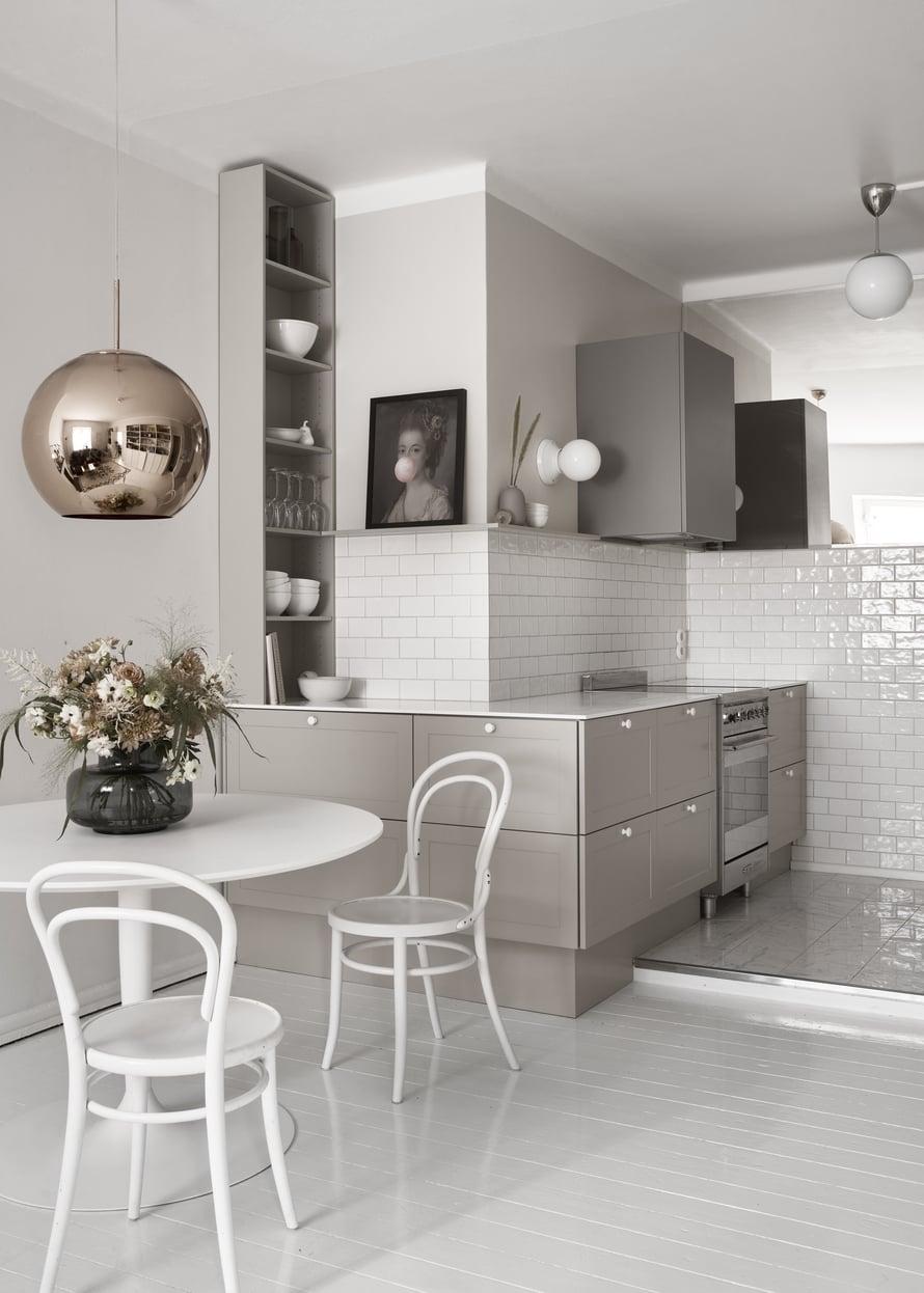Yläkaapittomuus ja peili tekevät keittiösyvennyksestä keveän. Liesituuletinkaappi on Nixin mallistoa, ja seinävalaisimet ovat Ikean. Kukkakimppu on Johanna Pauliina Designin toteuttama.