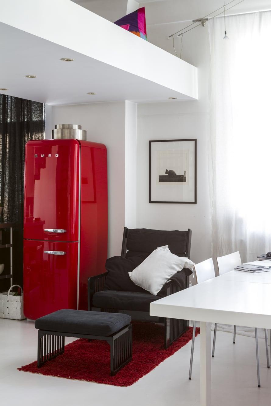 Valaistus on upotettu parven alapuolelle. Punainen jääkaappi on Smegin. Musta nojatuoli ja rahi ovat Ben af Schultenin. Seinällä on Pentti Kaskipuron grafiikkatyö. Valkoiseksi maalattu, pitkä pöytä oli 1950-luvulla Artekin neuvottelutiloissa, ja sen on suunnitellut Alvar Aalto. Tuolit ovat Antti Kotilaisen Piiroiselle suunnittelemat.