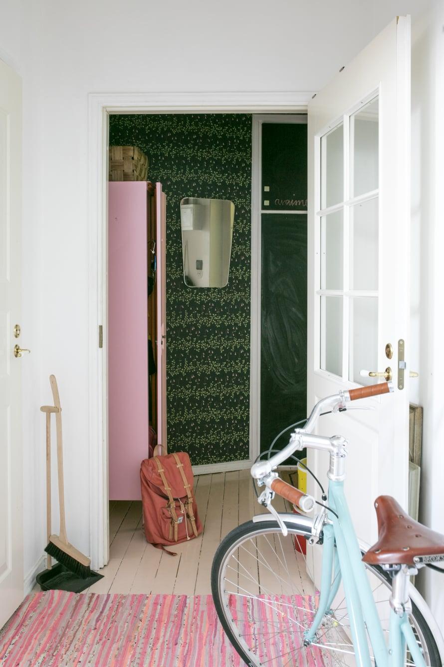 Eteinen on ainoa huone, jossa on tumma värimaailma. Sandbergin Linnea-tapetissa kukkivat vaaleanpunaiset vanamot. Vanha työmaakaappi löytyi Lahtelaisesta kirpputori Kisällistä. Pelagon kaunista Capri-pyörää Iina ei raaski piilottaa kellariin.