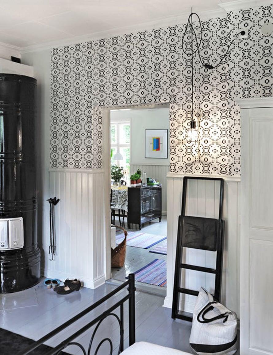 <p><p>Mustaksi maalattu pönttöuuni ei jää huomaamatta makuuhuoneen nurkassa. Tikkaat ja valaisin ovat Design House Stockholmin valikoimista.</p></p>