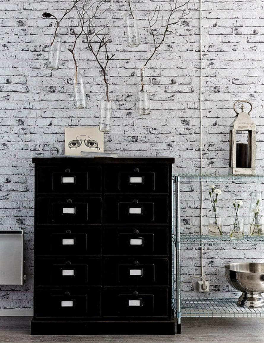 Ala- ja yläkerran pitkät seinät tapetoitiin valkoisella tiili-imitaatiotapetilla. Musta sopii tilaan valkoisen hyväksi kaveriksi. Vanha lipasto sulkee sisäänsä suuren määrän tavaraa.
