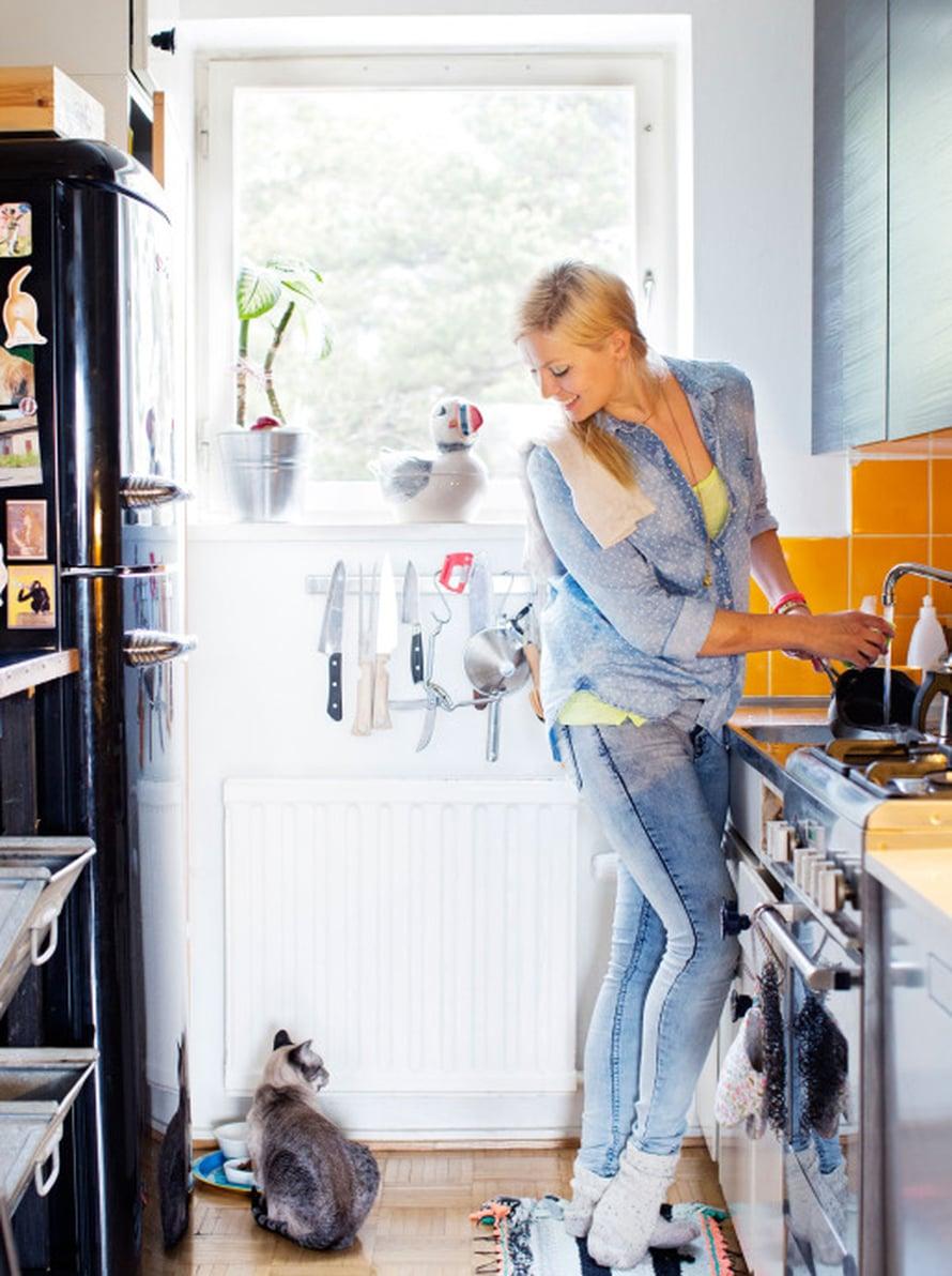 """""""Haaveilen modernista keittiöstä. 1950-luvun keittiöni on epäkäytännöllinen mutta kodikas. Olen lisännyt sinne tason ja hyllyjä, koska säilytystilaa on liian vähän ja tiskikone on väärässä paikassa. En uudista keittiötä ennen taloyhtiömme putkiremonttia."""" Stinky-kissalla on ruokatunti."""