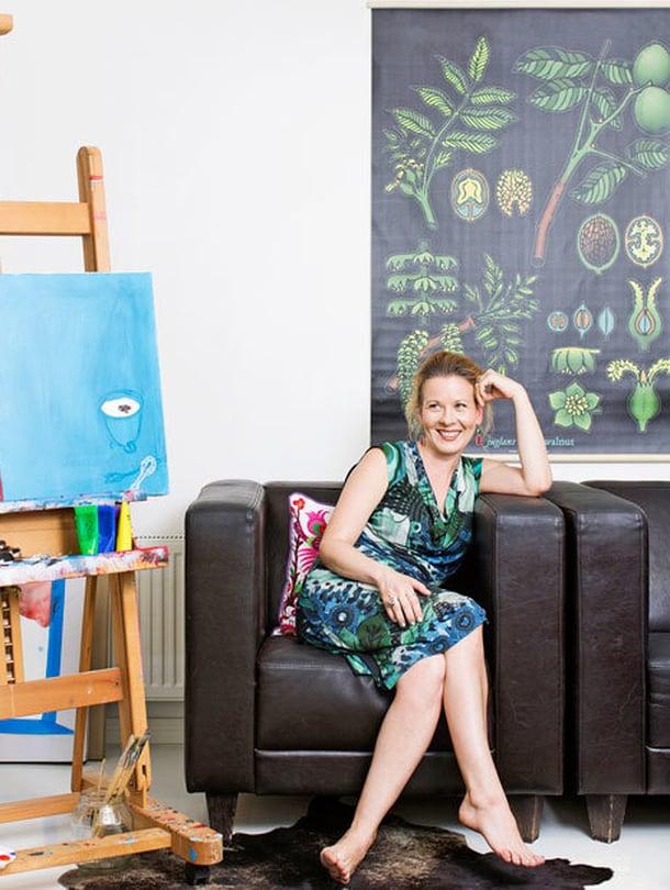 """""""Alakerta on firmani tila, jossa työskentelen eli kirjoitan, maalaan ja pidän pieniä workshopeja ja luentoja. Rohkaisen oppilaita ottamaan luovuutensa käyttöön ja luottamaan siihen. Oma akryylityöni on nimeltään Hirveän hienot juhlat. Nahkanojatuolit hankin yli kymmenen vuotta sitten, ja ne kestävät varmaan ikuisesti. Kasvitaulun löysin Ikeasta."""""""