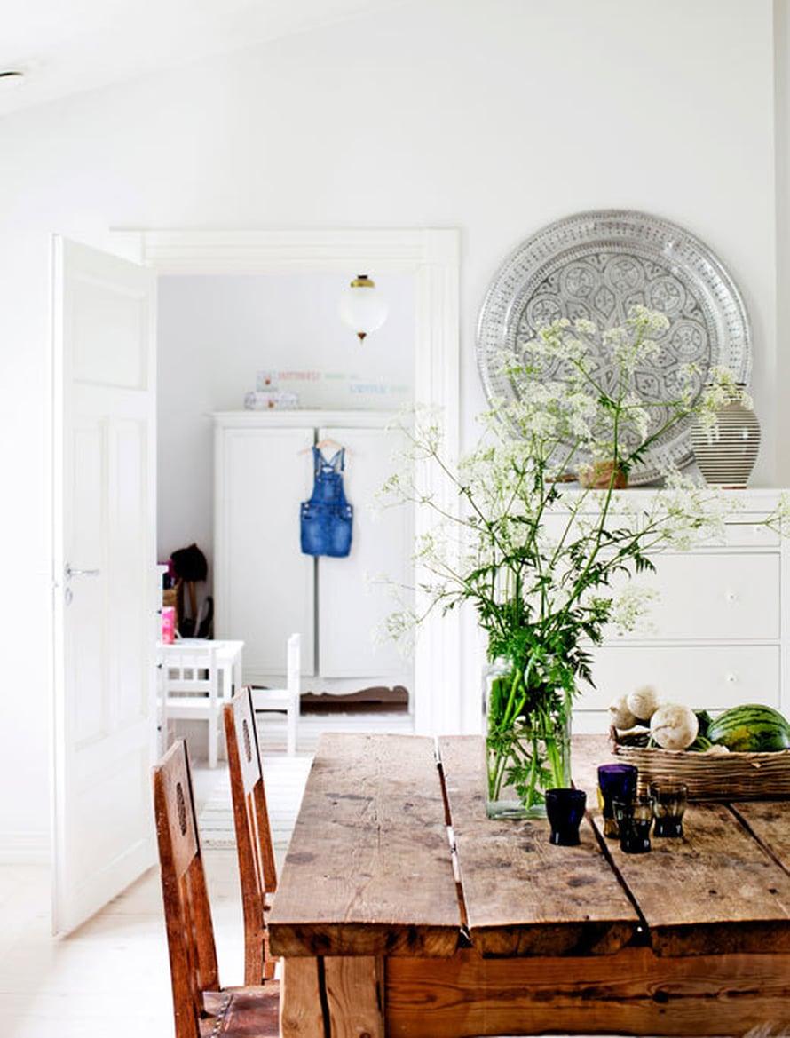 <p><p>Lankuista tehdyn pöydän takana olevan piirongin päällä lepää Tine K Homen marokkolaistyylinen metallitarjotin. Taustalla näkyy tyttären huone, jota keventävät valkoiseksi maalatut vanhat kalusteet.</p></p>