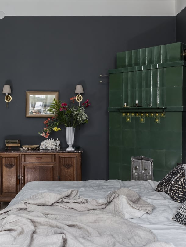 Makuuhuoneen kakluunin syvä vihreä sävy määritti muun huoneen värityksen. Marmorikantinen lipasto löytyi vanhojen tavaroiden liikkeestä. Sängyn tekstiilit luovat mielenkiintoisen pintojen yhdistelmän tummaa taustaa vasten.