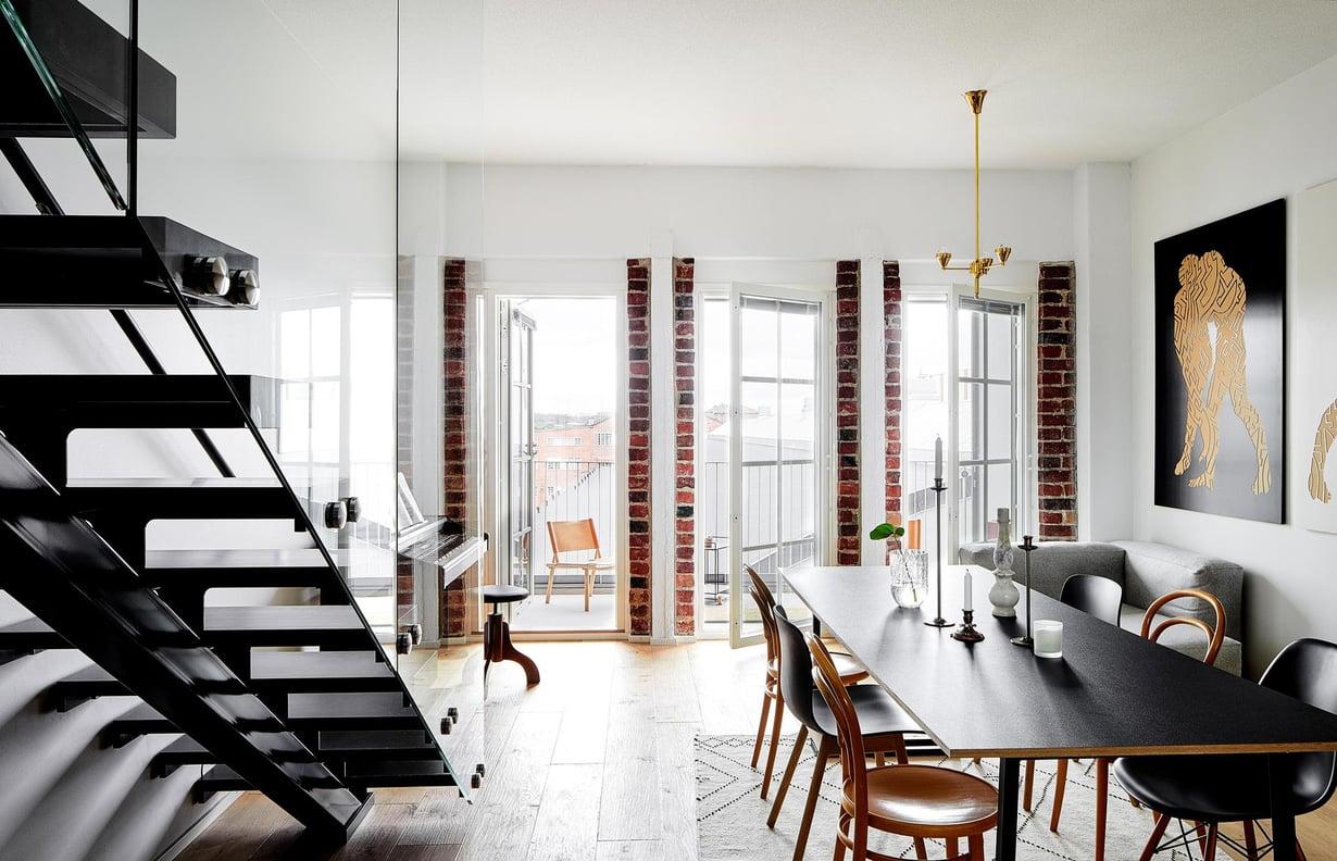 Ruokatilan pöytä koottiin jo vanhassa kodissa olleista Bedesignin pukkijaloista, joiden päälle sahautettiin sopivan kokoinen vanerilevy. Tuolit Anna on koonnut vuosien mittaan, muutama on kirpputorilta, mustat Hayn ja Eamesien tuoleja. Mum'sin matto on Saanan ja Ollin suunnittelema.