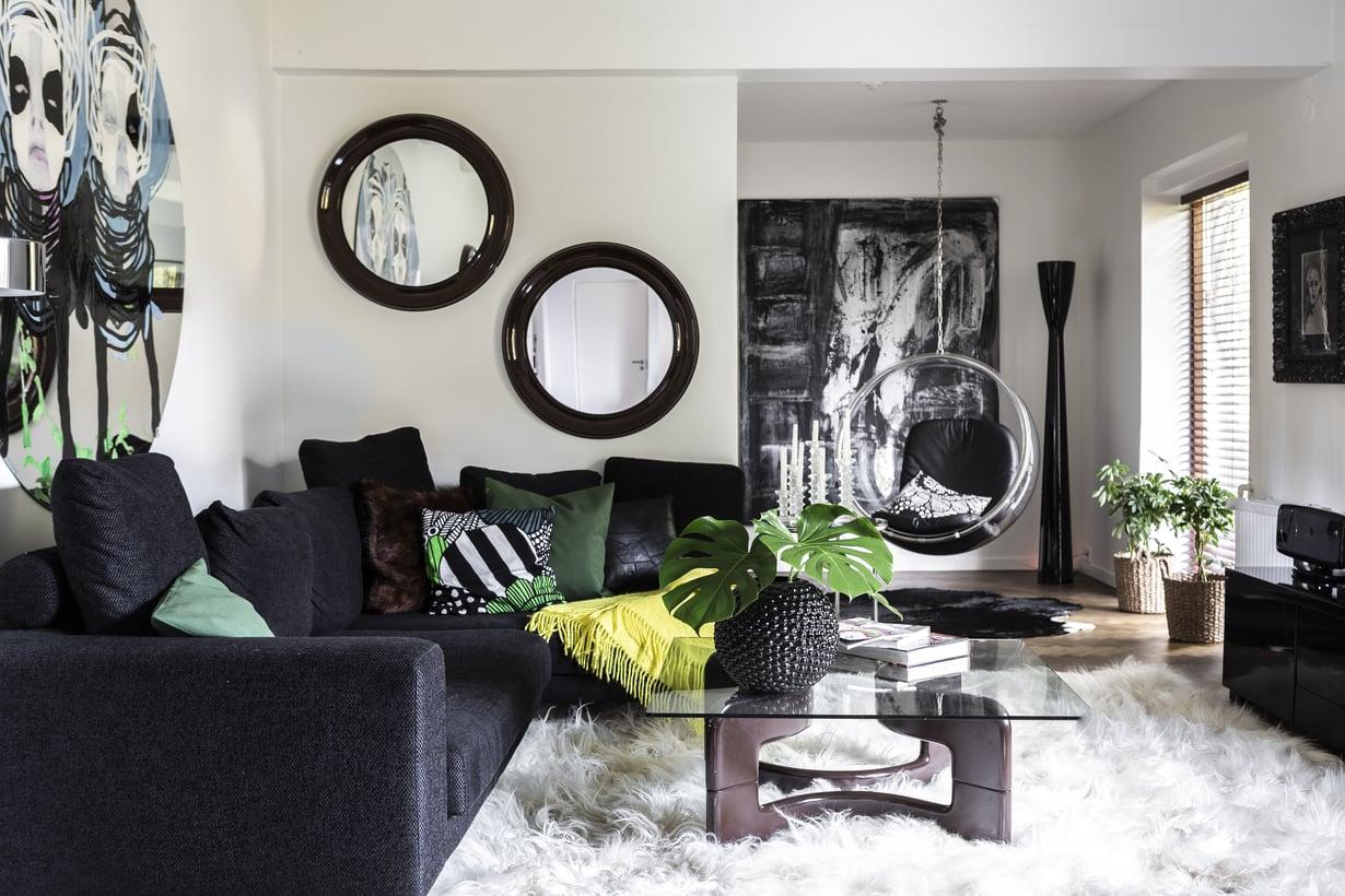 Muovijalkainen lasipöytä oli ystävättären mielestä niin ruma, että vain Marja saattaisi löytää sille käyttöä. Suuri kulmasohva löytyi Habitatista. 70-luvun peilit ovat vintagekaupasta. Nurkan musta Artemide Carrara -lattiavalaisimen on suunnitellut Alfredo Häberli. Pöydän vaasi Svensk Tennistä.