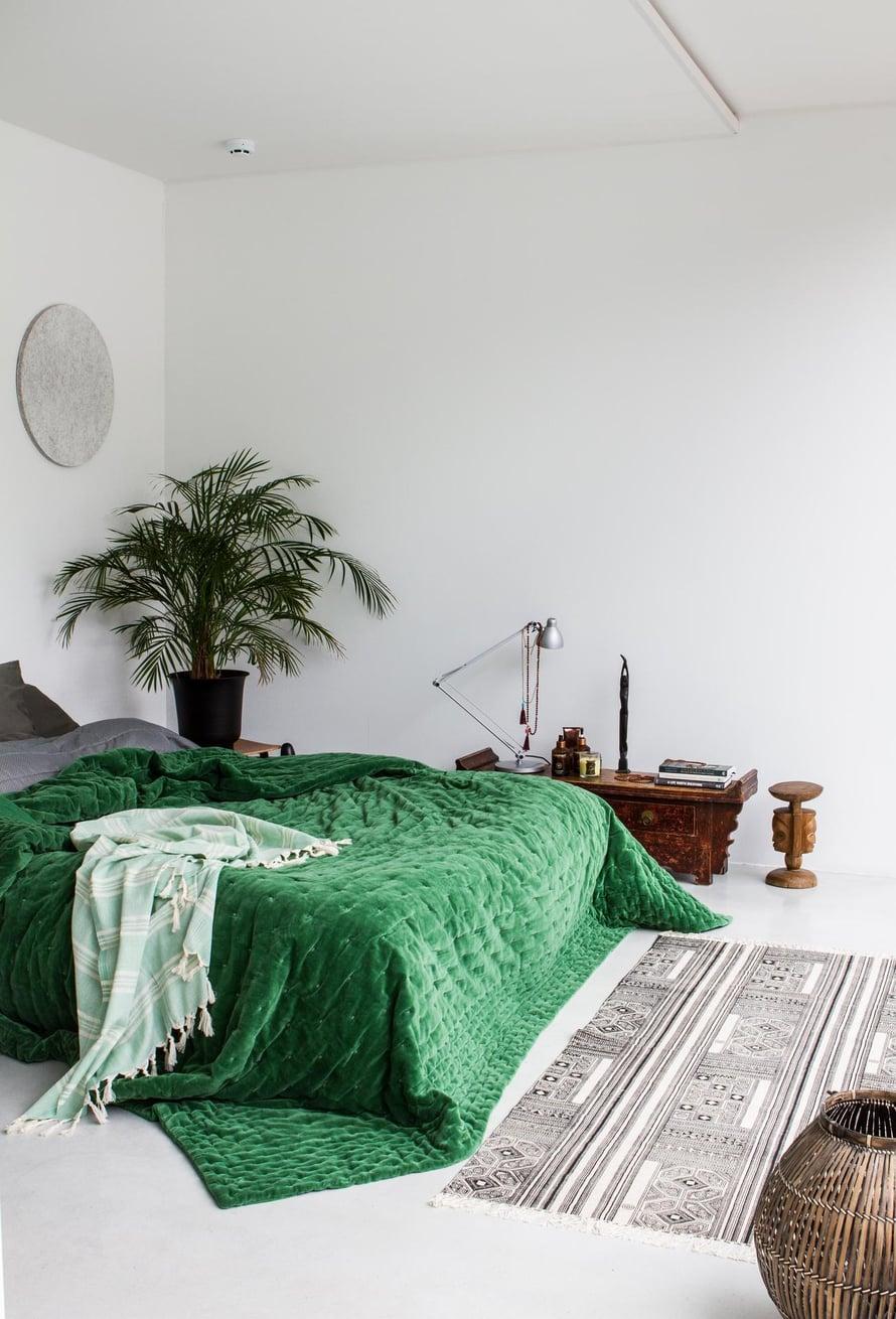 Makuuhuoneeseen valittiin vihreän Mokon päiväpeiton tuomaan energiaa. Seinässä sängyn päällä on turpeesta valmistettuja akustiikkalevyjä.