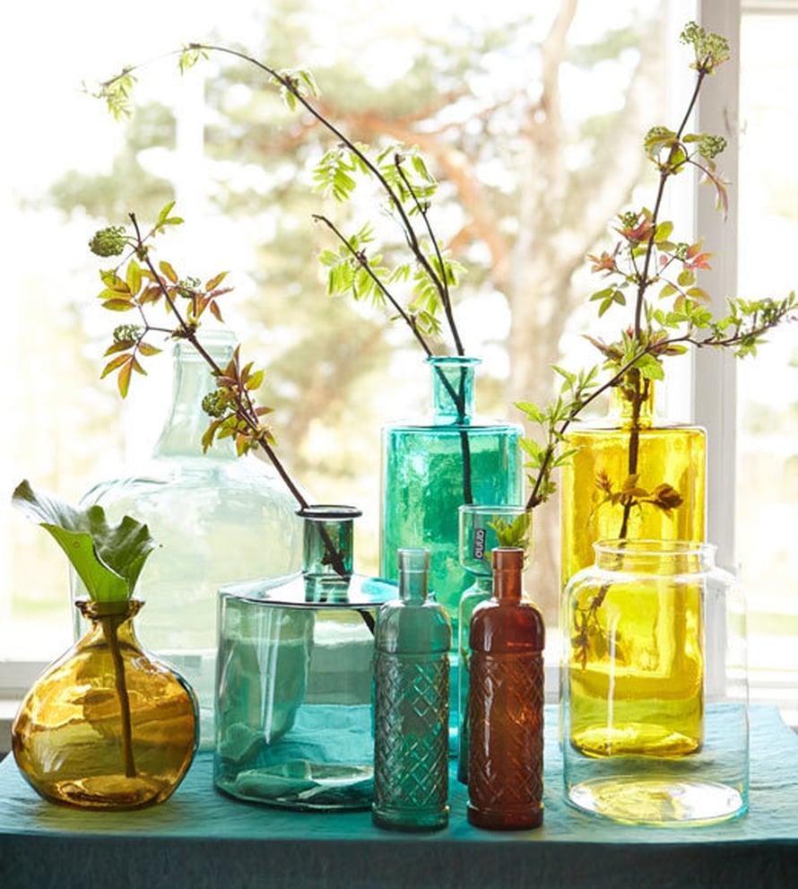 <p><p>Anno-kokoelman värikkäillä lasipulloilla ja muutamalla oksalla saa aikaan näin kauniin asetelman. Kuva ja tuotteet: Kodin1</p></p>