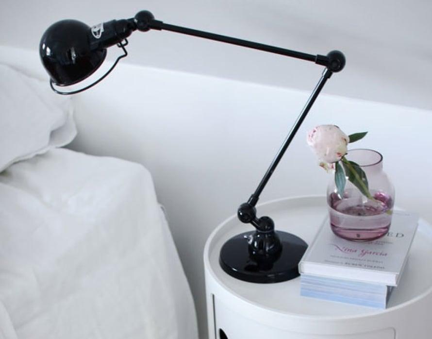 Pastelliset yksityiskohdat ja yöpöydälle asetettu pioni viimeistelevät huoneen tunnelman.