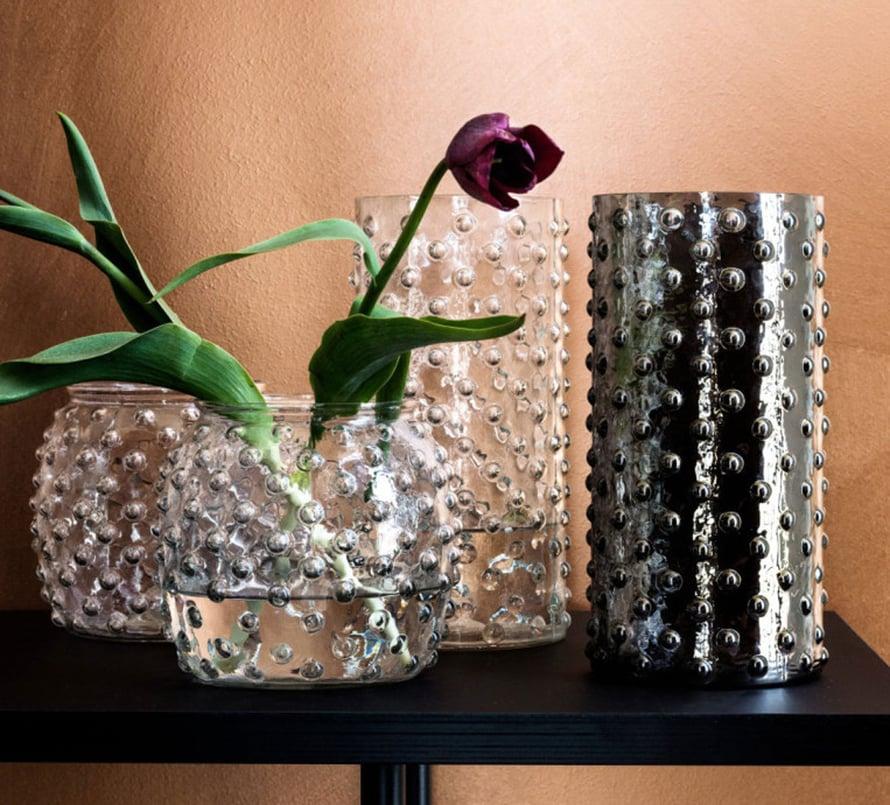 Tee asetelmia samanhenkisistä maljakoista ja täytä ne maltillisesti yksittäisillä kukilla, näin tunnelma pysyy seesteisenä. Kuva: H&M Home.