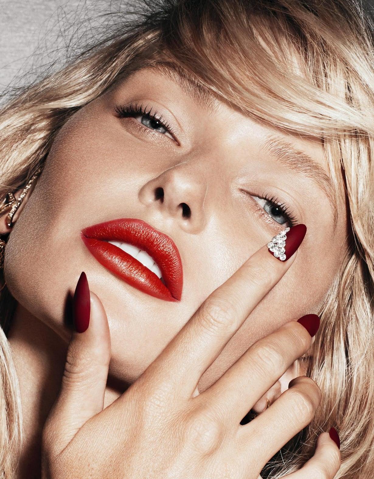 Huulimeikki pysyy, kun kuorit ja kosteutat huulesi ennen meikkausta. Täydellisesti rajatut Elsa Hosk -tyyliset huulet näyttävät aina luksukselta. Ne saat, kun taputtelet huulille ensin meikkivoidetta ja puuteroit huulten reunat kevyesti (puuteri estää punan karkaamisen). Sen jälkeen rajaa ja täytä huulet värittämällä huultenrajauskynällä. Tämä old school -tekniikka saa punan pysymään. Levitä  rajauskynän väristä huulipunaa. Kuvassa kynsissä Vero Krew Natural Diamondsin Rose- ja Clarity-timantteja
