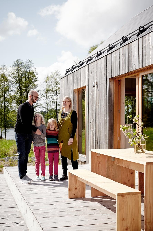 Sisäänkäynnin puolelle Mathias ja Sonja rakensivat terassin douglaskuusesta. Perheen takana siintää läheinen järvi.