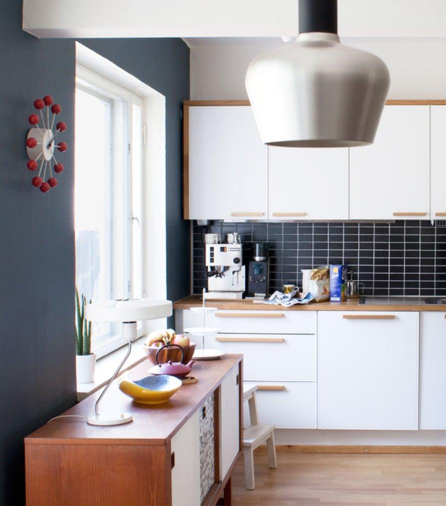 Vintagetyylisen keittiön ikkunaseinä maalattiin siniseksi, sävy S431. Sininen sopii erityisen hyvin puunvärien seuraksi. Välitila kaakeloitiin tummansininsillä Cello Minimal -laatoilla. Valkoiset kaapistot saivat 1950-luvun tyyliin sopivan ilmeen, kun ne reunustettiin puuraameilla ja vetimillä. Kuva Kia Orama.