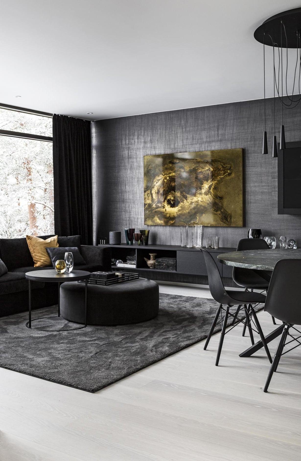 """""""Mancavessa"""" on paljon Timon keräilemää designlasia, jota varten Heini rakensi koko seinän levyisen kaapiston. Himmeästi hohteleva Elitiksen tapetti on painettu metallifoliolle. Slettvollin sohva, samettirahi ja sohvapöytä hankittiin Ruotsista. Messinkilevylle tehty työ on Toni R. Toivosen. Pyöreän, Per Söderbergin suunnitteleman No Early Bird -pöydän päällä on Morosinin riippuvalaisin."""